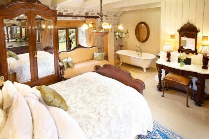 Large opulent master bedroom with roll top bath